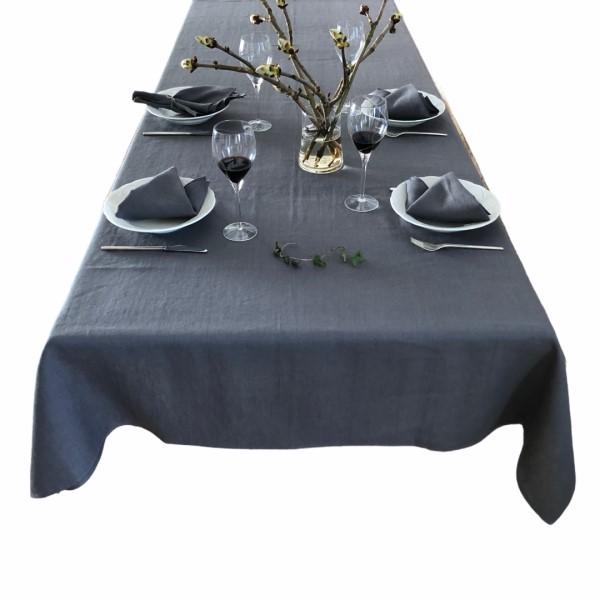 Her vises et dækket bord med en grå hørdug og grå hørservietter fra ecoinvent. På midten af bordet står en buket blomster.