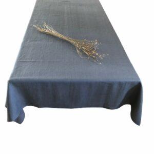 Her vises en smuk grå hørdug fra ecoinvent. dugen ligger på et bord og er pyntet med en buket tørret hørplanter