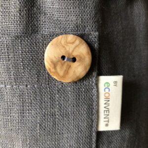 Nærbillede af fin naturtræknap ved lomme på hørforklæde Carbon grey fra ecoinvent.