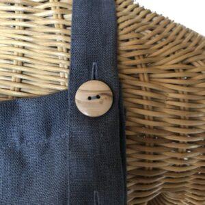 Nærbillede af fin naturtræknap på hørforklæde Carbon grey fra ecoinvent.